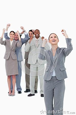 Cheering businesswoman with team behind her