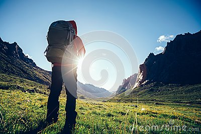 Woman hiker with backpack hiking on high altitude mountain Stock Photo