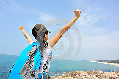 Cheering woman open arms at seaside rock