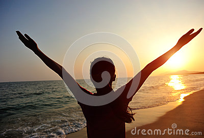 Cheering woman open arms to sunrise at sea