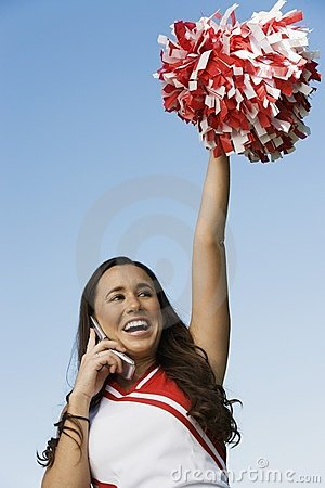 Cheerleader rising pom-pom, talking on cell