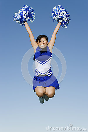 Free Cheerleader With Pompoms In Midair Against Sky Stock Photos - 33828913