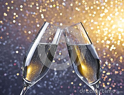 Cheers with two champagne flutes with golden bubbles on light bokeh background