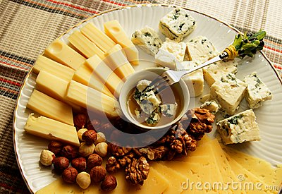 Cheese plate with several kinds of cheese, nuts and honey,top view