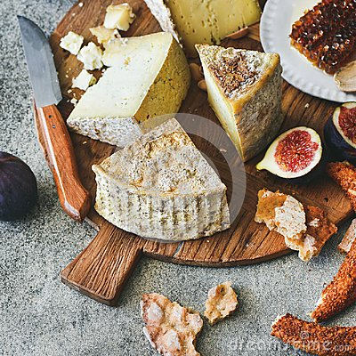 Cheese assortment, figs, honey, fresh bread and nuts, square crop Stock Photo