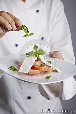 Chef adding greens to dish