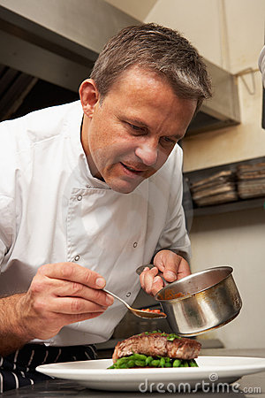 Chef Adding Sauce To Dish In Restaurant