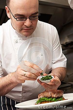 Chef Adding Seasoning To Dish In Kitchen