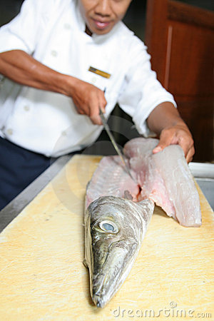 Chef butchering barracuda fish