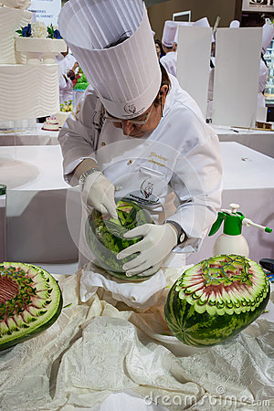 Chef carves a watermelon at Host 2013 in Milan, Italy Editorial Stock Photo