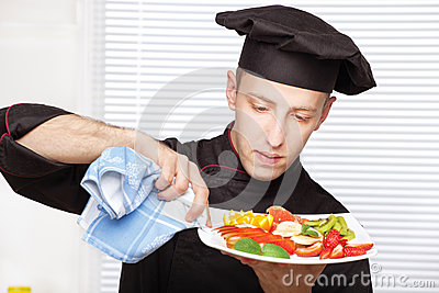Chef cleaning edge of a fruit plate with cloth