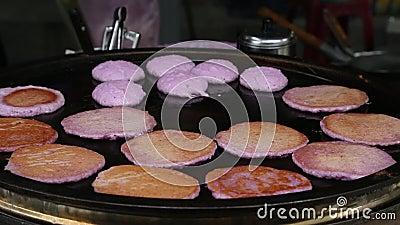 Flipping hamburger of purple meat on a frying pan in night market of Taipei