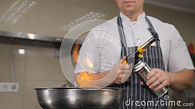 Chef cozinhando na cozinha do restaurante Cozinhar com chamas, Curso lento de chamas que se erguem para fora da frigideira Hd filme