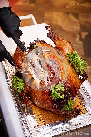 The chef cuts the turkey on a tray in a restaurant Stock Photo