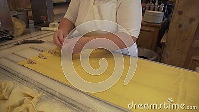 Chef de cozinha fêmea prepara ravioli manualmente com carne picada tradicional prato nacional italiano video estoque