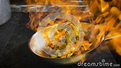 Chef, der Gemüse brät Kognak wird in der Wanne angezündet Öffnen Sie Feuer in der Küche stock footage