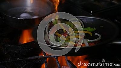 Chef et feu professionnels Cuisson des l?gumes et de la nourriture au-dessus d'un feu ouvert sur un fond fonc? clips vidéos