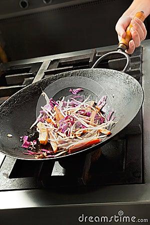 Chef faisant cuire des légumes dans le wok