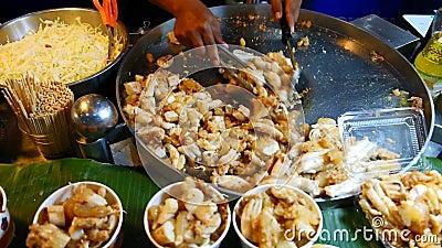 Chef faisant cuire les oeufs faits sauter à feu vif de calmar à vendre, Thaïlande