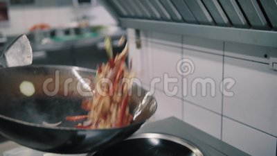 Chef fries food in a wok pan. In the kitchen stock video footage