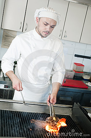 Chef frying beef steak on grill