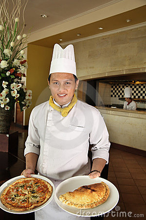 Chef holding pizza at restaurant