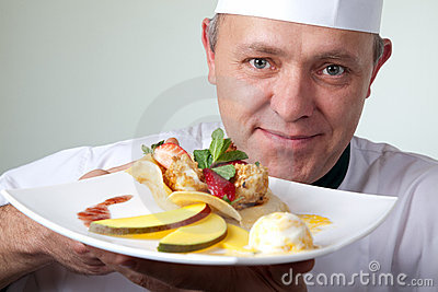 Chef holding plate cheese fruit dessert