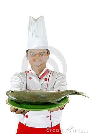 Chef holding raw fish on a green plate