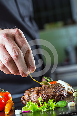 Free Chef In Hotel Or Restaurant Kitchen Cooking, Only Hands. Prepared Beef Steak With Vegetable Decoration Royalty Free Stock Photos - 52784308