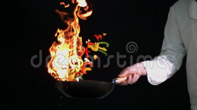 Chef-kok flambeing peper in wok stock footage