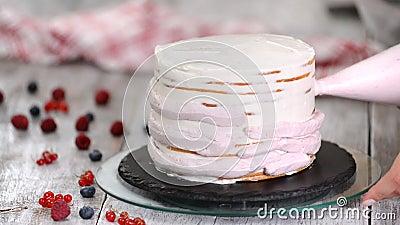 Chef pâtissier piquetant de la crème sur une couche de gâteau d'éponge banque de vidéos