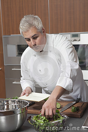 Chef Preparing Salad In Commercial Kitchen