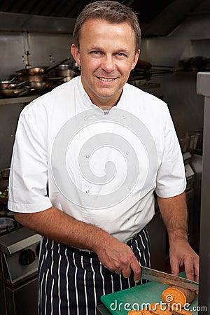 Chef Preparing Vegetables In Restaurant Kitchen