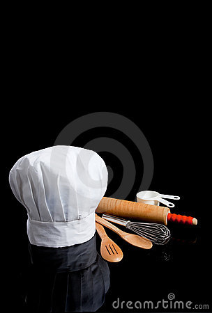 A chef s toque with kitchen utensils on black