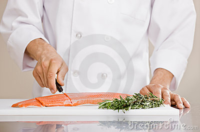 Chef slicing raw salmon to prepare for meal