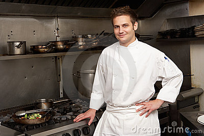 Chef Standing Next To Cooker In Kitchen