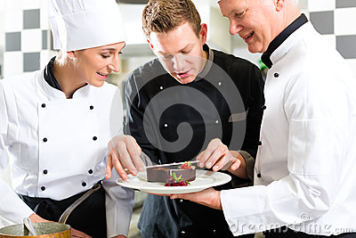 Chef team in restaurant kitchen with dessert