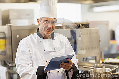 Chef using his digital tablet and looking at camera