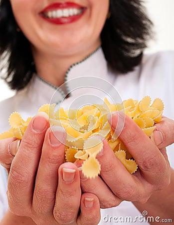 Chef woman holding macaroni handful