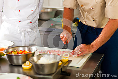 Chefs preparing fish in restaurant or hotel kitchen