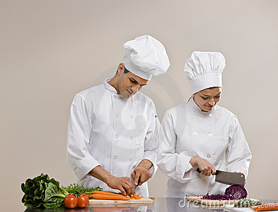 Chefs in toques preparing and chopping food