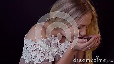 Cheiros de feijões de café A jovem mulher em um fundo preto inala o aroma de feijões de café filme