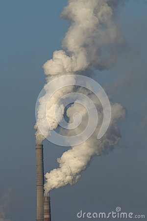 Cheminée d évacuation des fumées de station de la chaleur contre le ciel bleu