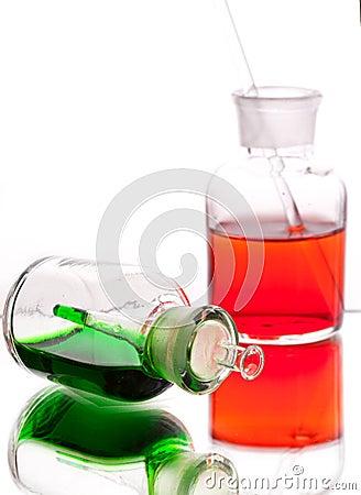 Chemistry laboratory glassware with colour liquids on white back