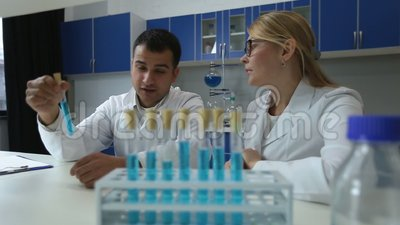 Chemists analyzing test tubes with liquid in lab stock video