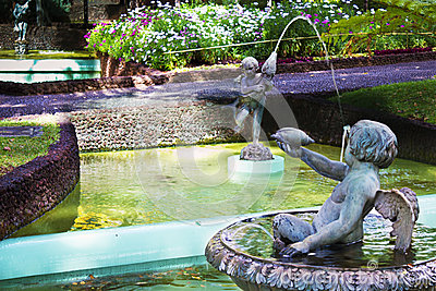 Cherubs water fountain in tropical garden