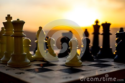 chess board game concept of business ideas and competition and strategy ideas. Chess figures on a chessboard outdoor sunset backgr Stock Photo