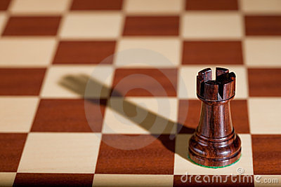 Chess piece - a black rook on a chessboard.