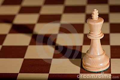 Chess piece - a white king on a chessboard.