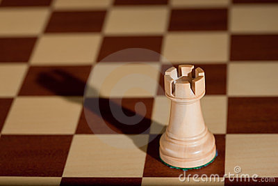 Chess piece - a white rook on a chessboard.